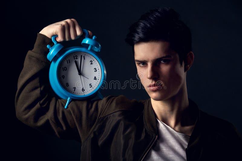 Homem novo isolado em um conceito cinzento do estúdio da parede que mostra o tempo fotos de stock royalty free