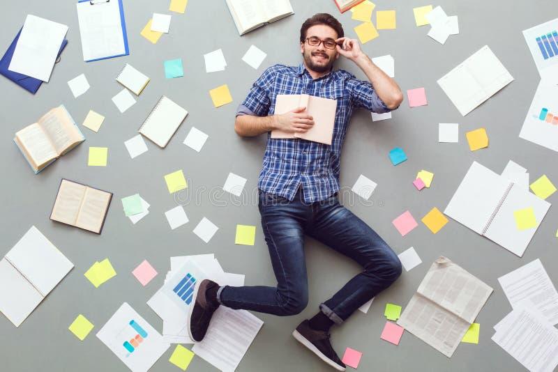 Homem novo isolado no fundo cinzento com os papéis e as notas que guardam o livro foto de stock