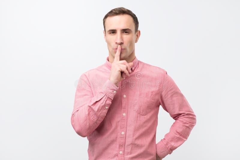 Homem novo italiano na camisa cor-de-rosa que faz um gesto do silêncio fotografia de stock