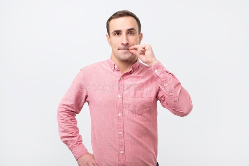 Homem novo italiano na camisa cor-de-rosa que faz um gesto do silêncio imagem de stock royalty free
