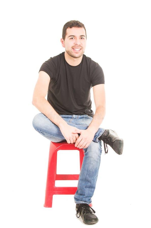 Homem novo latino que senta-se no tamborete vermelho foto de stock