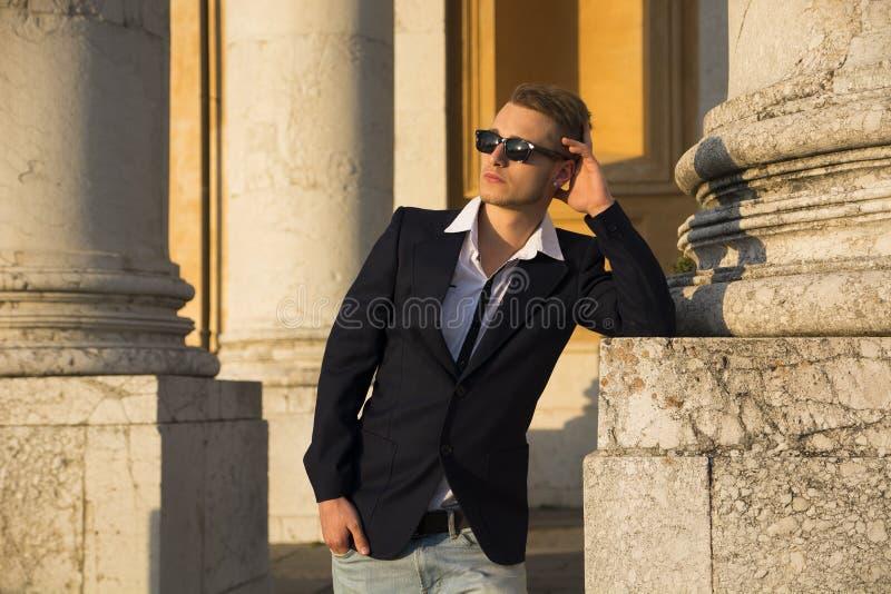 Homem novo louro considerável com as colunas de mármore atrás dele fotos de stock royalty free