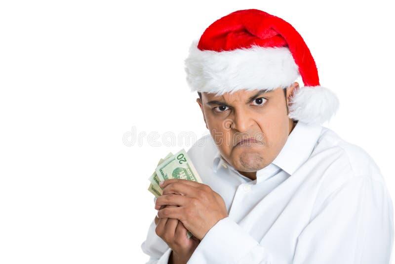 Homem novo mal-humorado no chapéu de Santa possessivo sobre seu dinheiro imagem de stock