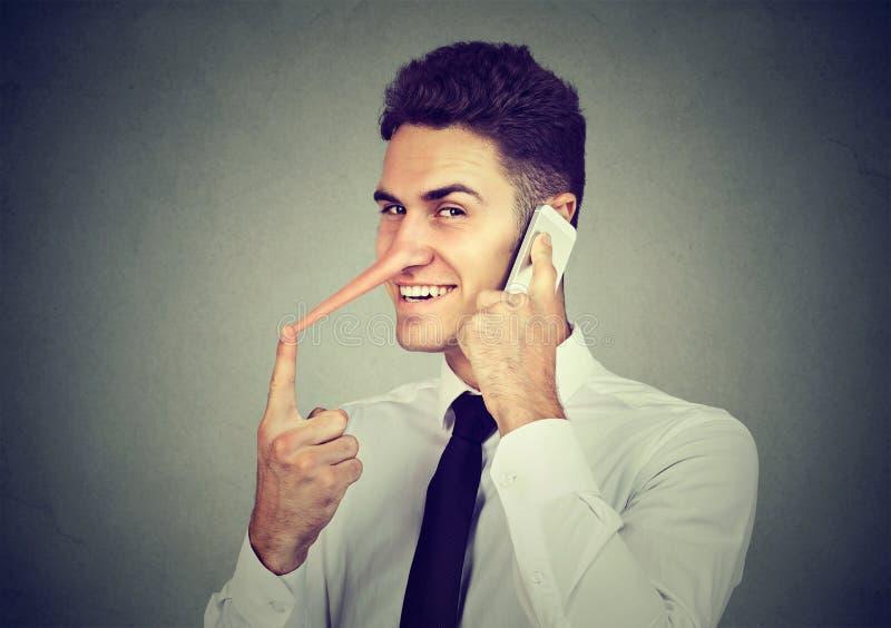 Homem novo manhoso com nariz longo que fala no telefone celular no fundo cinzento da parede Conceito do mentiroso fotografia de stock royalty free