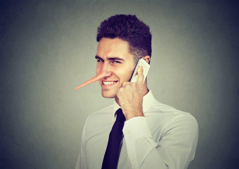 Homem novo manhoso com nariz longo que fala no telefone celular no fundo cinzento da parede Conceito do mentiroso fotografia de stock