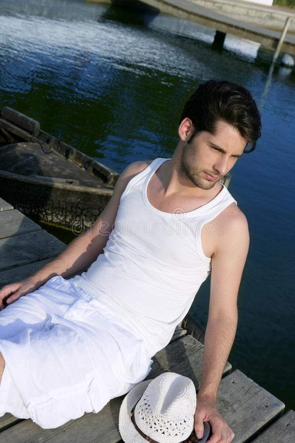 Homem novo mediterrâneo relaxado no cais de madeira fotografia de stock