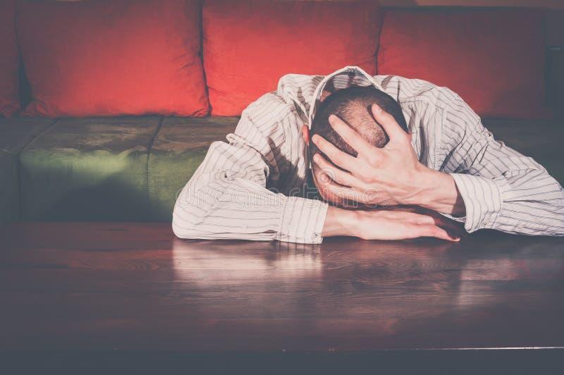Homem novo miserável que senta-se apenas em sua sala Grito triste do homem imagem de stock royalty free