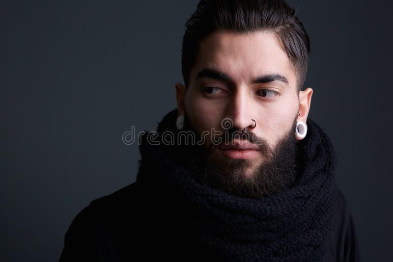 Homem novo moderno com barba e perfurações foto de stock