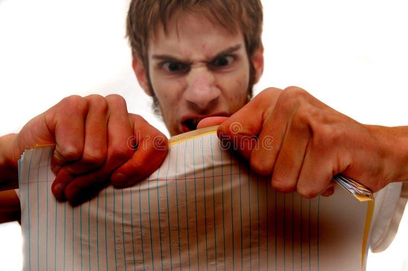 Homem novo muito irritado que tenta rasgar papéis foto de stock royalty free