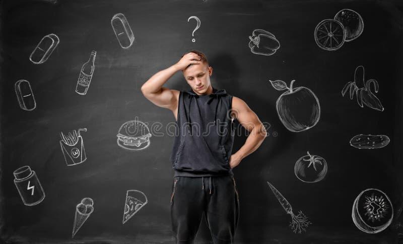 Homem novo Muscled que pondera que escolher: sucata ou alimento saudável foto de stock royalty free