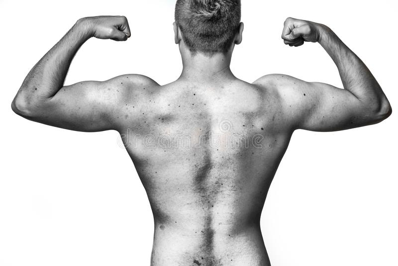 Homem novo muscular apto que dobra seus músculos imagem de stock royalty free
