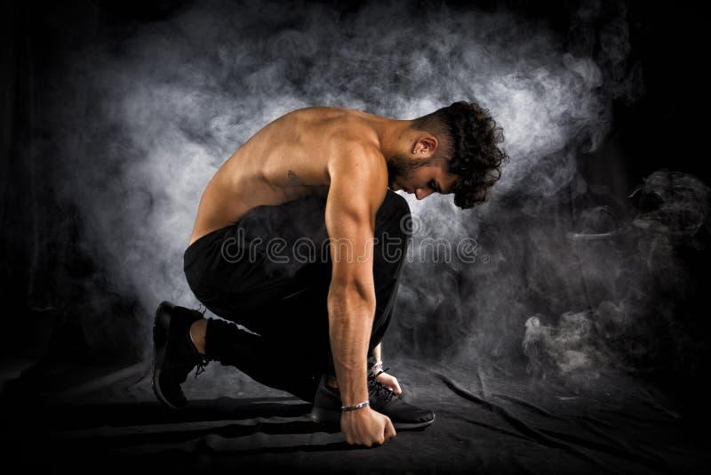 Homem novo muscular descamisado considerável que ajoelha-se para baixo no preto foto de stock royalty free