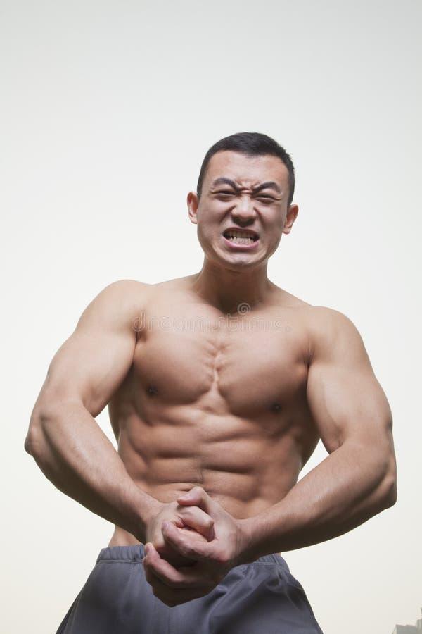Homem novo, muscular, descamisado que rosna e que dobra seus músculos, tiro do estúdio imagens de stock royalty free