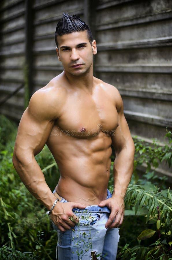 Homem novo muscular do latino descamisado nas calças de brim na frente do muro de cimento imagens de stock royalty free
