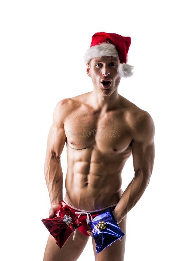 Homem novo muscular em um speedo e em um chapéu de Santa Claus com os 2 presentes do Natal imagens de stock