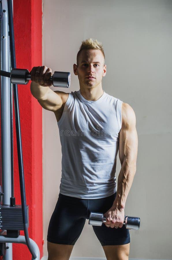 Homem novo muscular que dá certo no gym com pesos imagem de stock