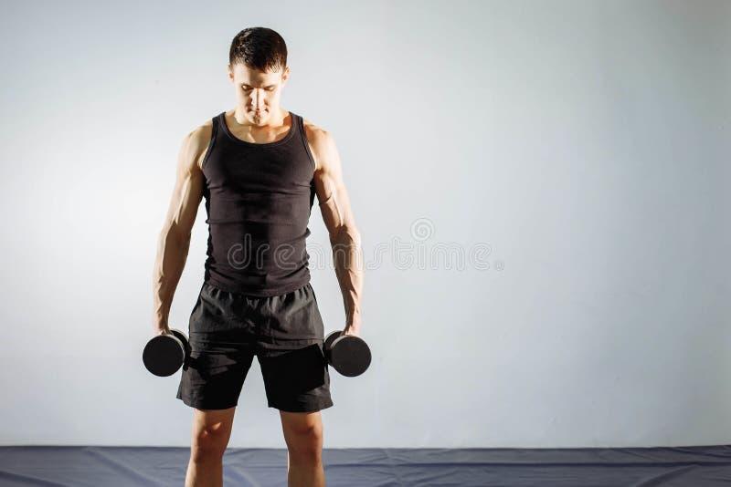 Homem novo muscular que faz o exercício pesado para o bíceps foto de stock