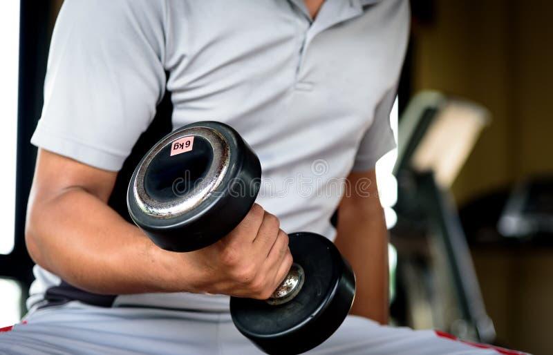 Homem novo muscular que faz o exercício pesado para o bíceps com D fotos de stock royalty free