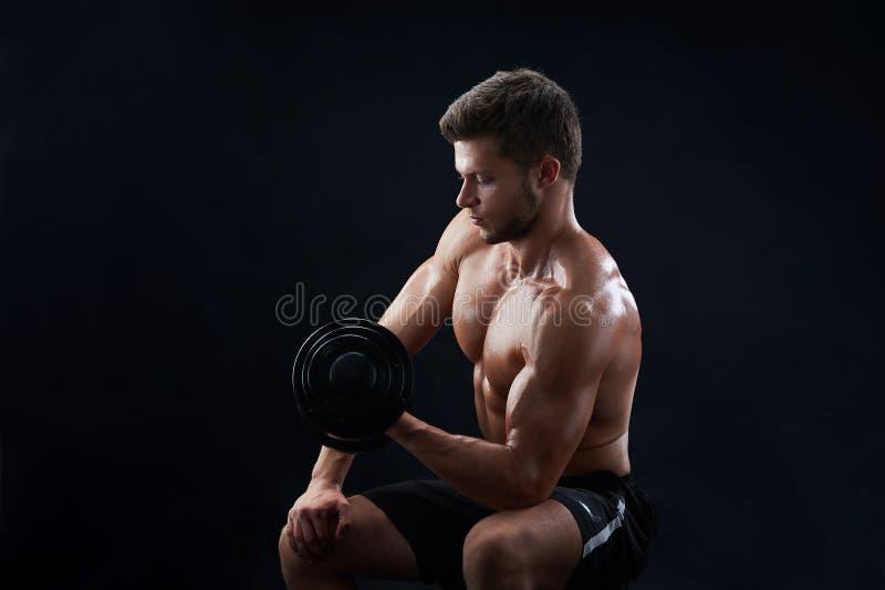 Homem novo muscular que levanta peso no fundo preto foto de stock