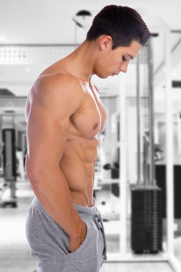 Homem novo muscular que olha abaixo do corpo do halterofilista do gym da aptidão do Abs fotos de stock
