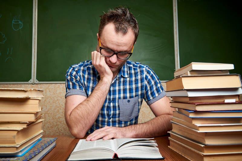 Homem novo não barbeado bagunçado nos vidros que lê um livro na tabela com as pilhas dos livros fotos de stock royalty free