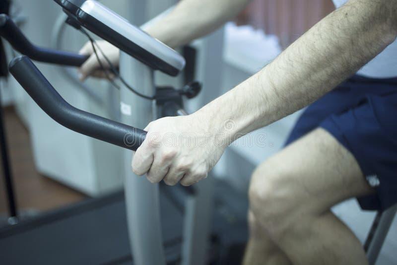 Homem novo na bicicleta de exercício imagem de stock