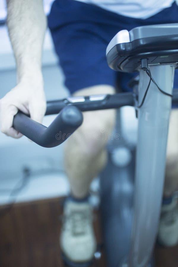 Homem novo na bicicleta de exercício foto de stock royalty free