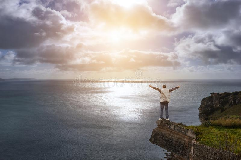 Homem novo na borda do ` s do penhasco, fole do oceano imagens de stock royalty free