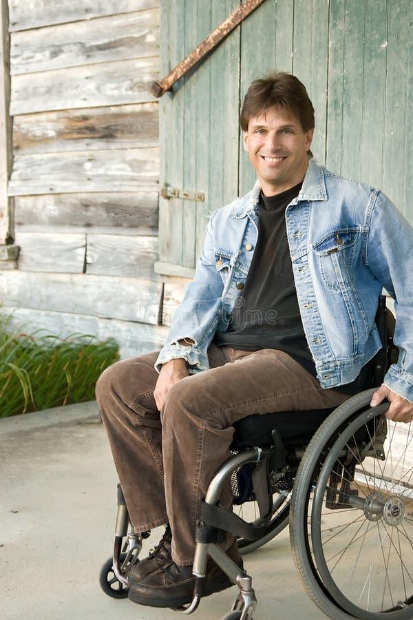 Homem novo na cadeira de rodas fotografia de stock royalty free