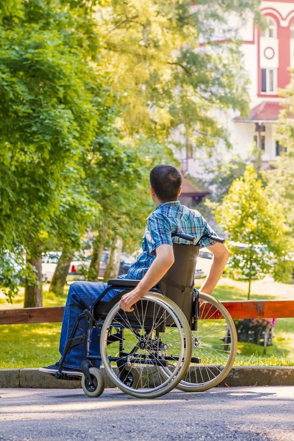 Homem novo na cadeira de rodas imagem de stock