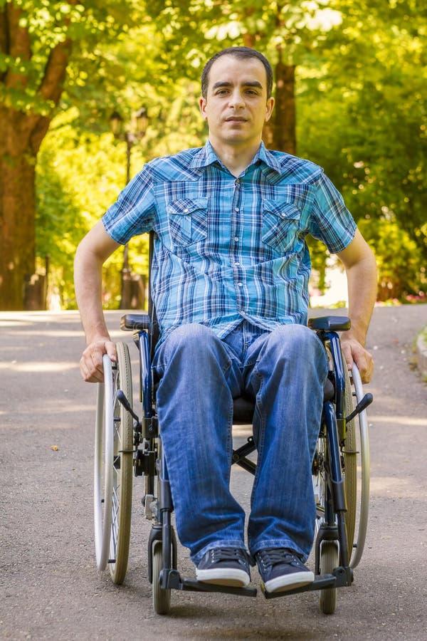 Homem novo na cadeira de rodas imagens de stock