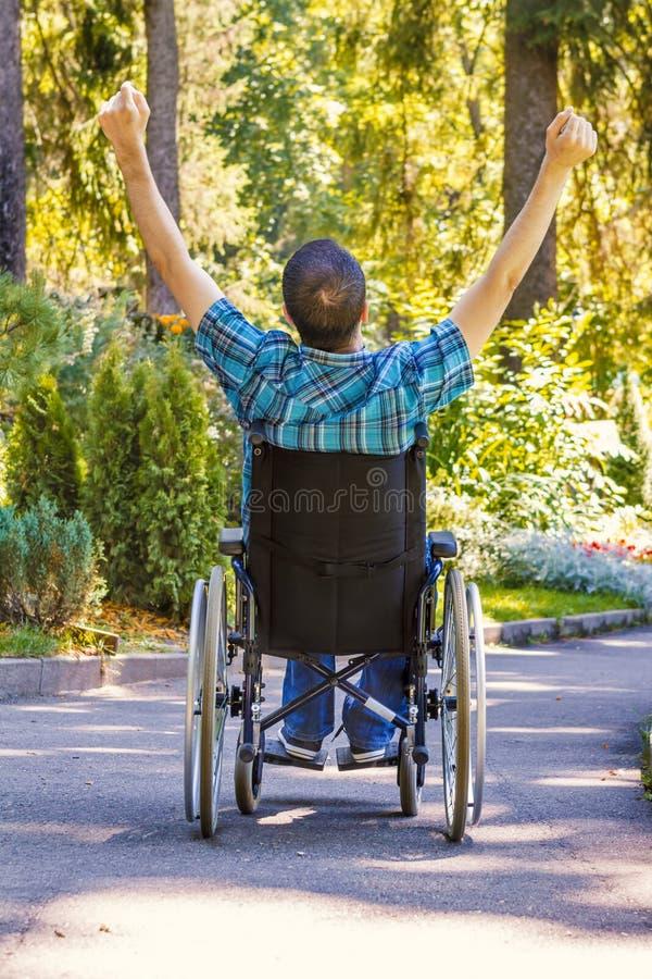Homem novo na cadeira de rodas com os braços abertos largos imagens de stock royalty free