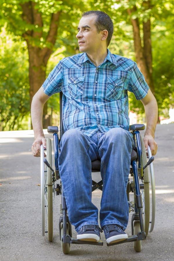 Homem novo na cadeira de rodas fora fotografia de stock