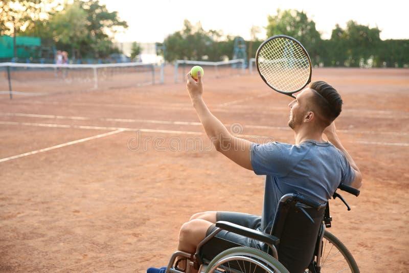Homem novo na cadeira de rodas que joga o tênis na corte fotografia de stock royalty free