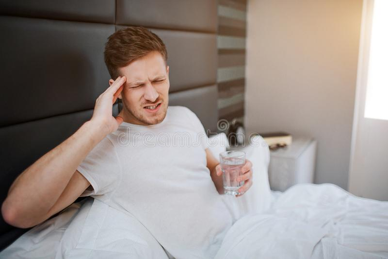 Homem novo na cama esta manhã Tem a dor de cabeça Vidro da posse do indivíduo da água à disposição Sofre Luz do dia O sol levanta foto de stock royalty free