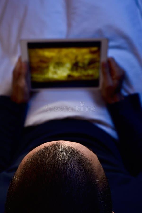 Homem novo na cama que olha um filme ou uma série em sua tabuleta fotografia de stock royalty free