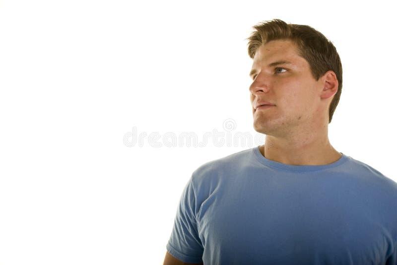 Homem novo na camisa azul que olha acima e para a direita fotografia de stock royalty free