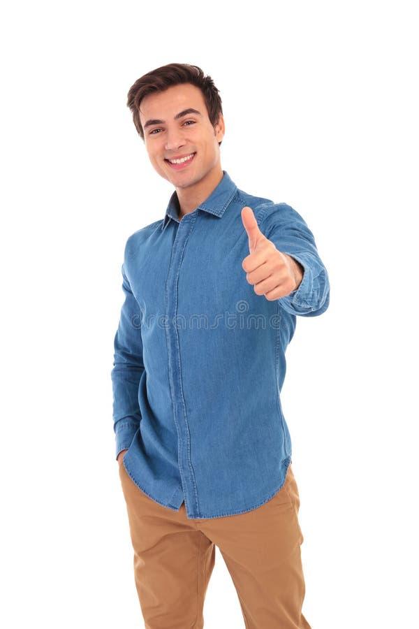 Homem novo na camisa das calças de brim que faz o gesto aprovado imagens de stock royalty free