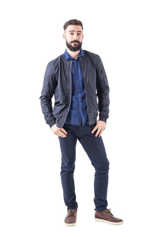 Homem novo na camisa e no revestimento de bombardeiro azuis com os polegares em uns bolsos que olham a câmera imagem de stock royalty free