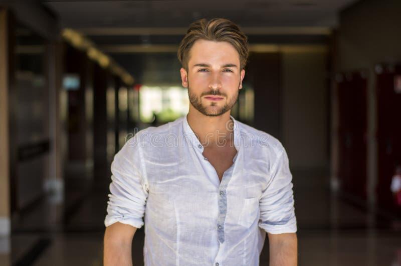 Homem novo na camiseta que está no corredor da escola fotografia de stock royalty free