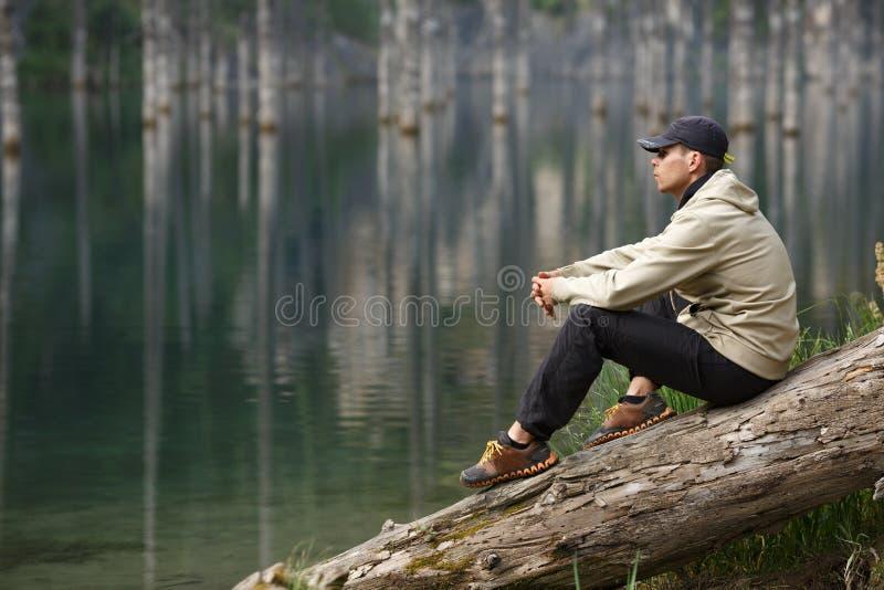 Homem novo na costa de um lago da montanha imagem de stock