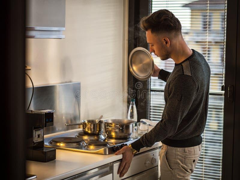 Homem novo na cozinha em casa, cozinhando no fogão imagem de stock royalty free