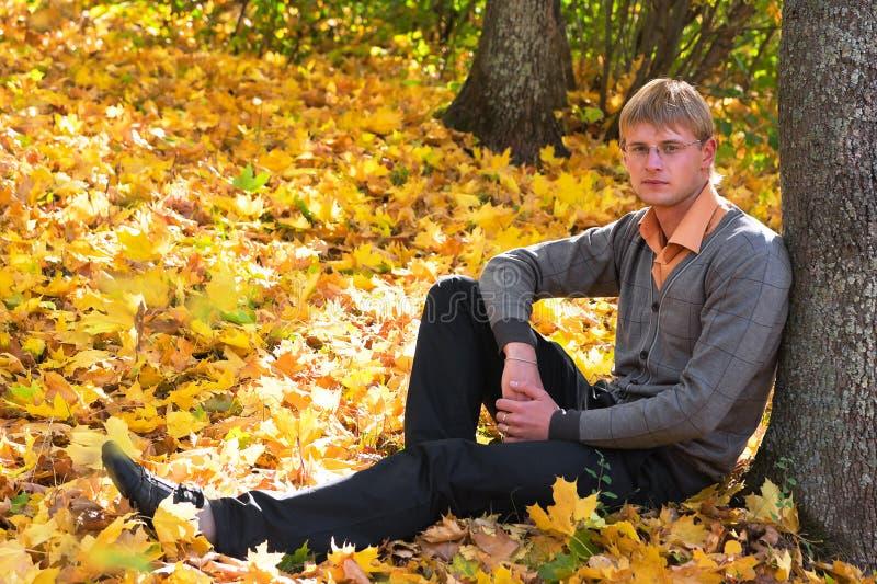 Homem novo na floresta do outono imagens de stock royalty free