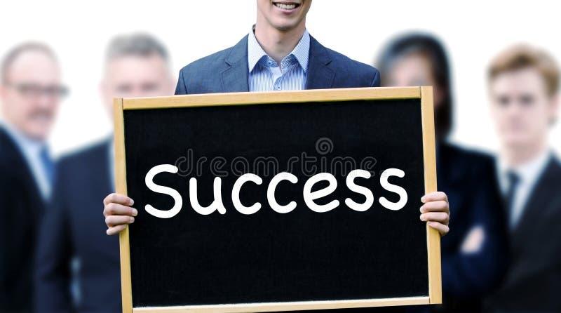 Homem novo na frente do grupo que guarda o sinal com sucesso da palavra fotografia de stock