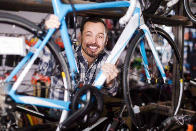 Homem novo na loja das bicicletas fotos de stock royalty free