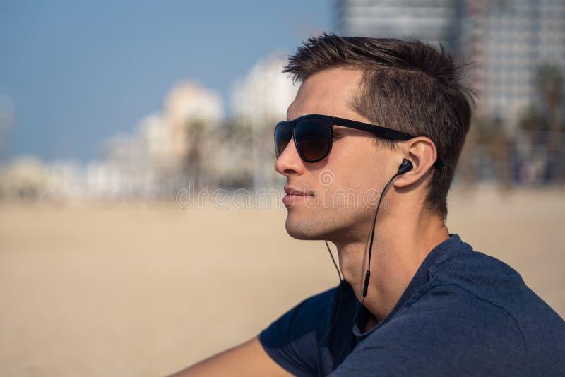 Homem novo na música de escuta da praia com fones de ouvido skyline da cidade como o fundo imagens de stock royalty free