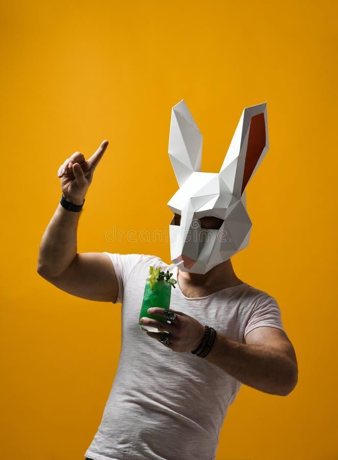 Homem novo na m?scara de papel do coelho e no t-shirt branco que bebe a bebida verde do cocktail fotografia de stock