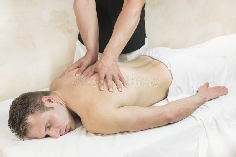 Homem novo na massagem dos tratamentos do bem-estar fotografia de stock