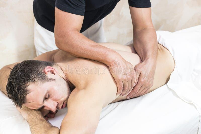 Homem novo na massagem dos tratamentos do bem-estar foto de stock royalty free