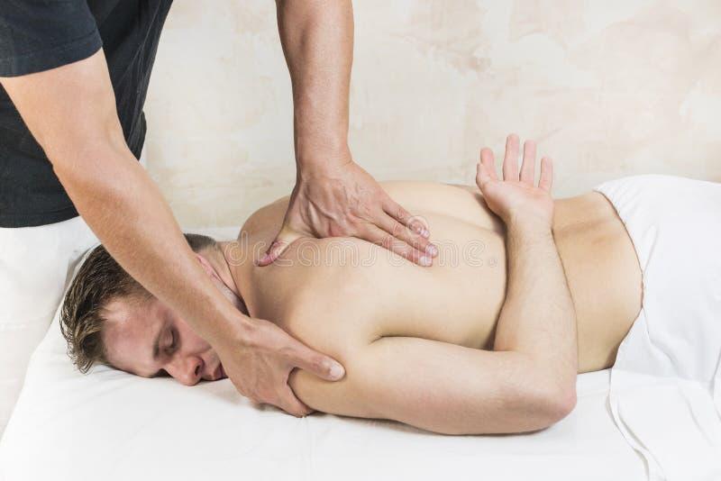 Homem novo na massagem dos tratamentos do bem-estar imagens de stock